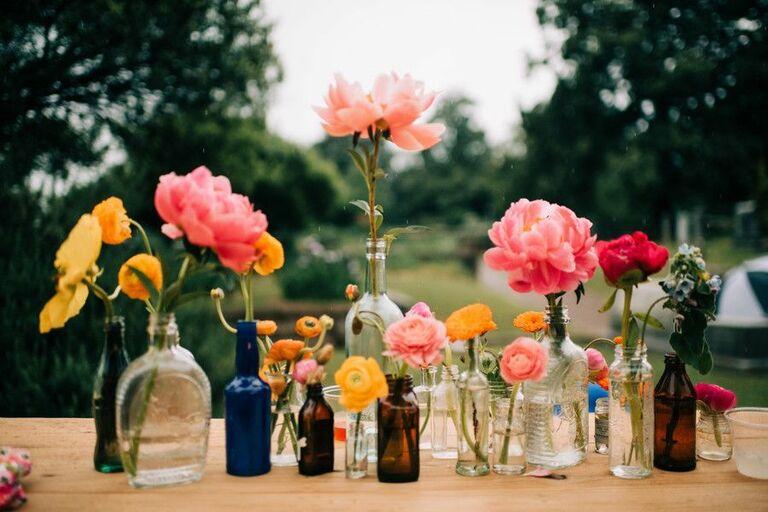 Peonies and ranunculus blooms in glass bottles