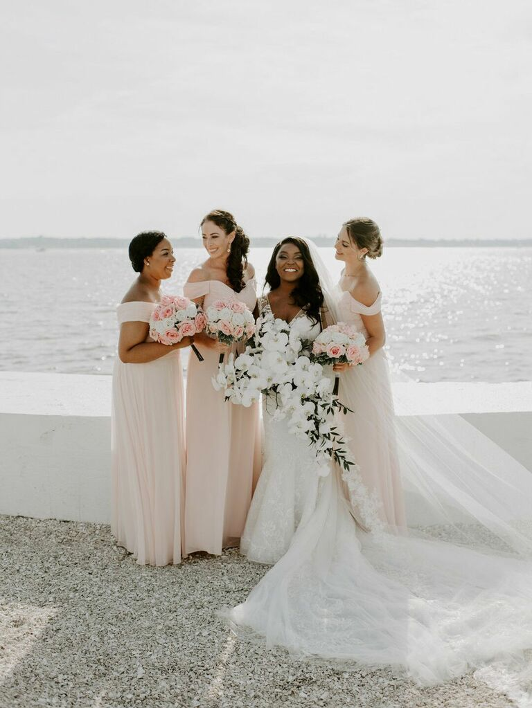 Bridesmaids and bride posing in front of scenic waterfront