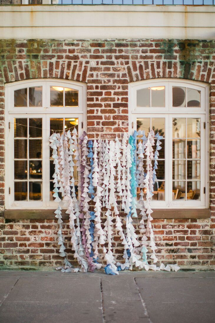 """I started experimenting with different types of paper and fell in love with the texture and flexibility of coffee filters,"" Charlee-Ann says. The backdrop for the ceremony was made by dying the filters various shades of blue and stringing them together in cone shapes along a rustic brick wall."