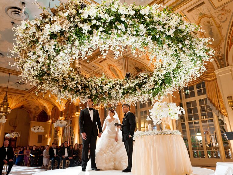 Bride and groom under large floral installation