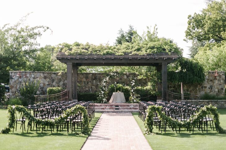 The outdoor ceremony took place among plenty of greenery at the Vintage House in Yountville, California. The most notable decoration was a hanging arch adorned with white blossoms.