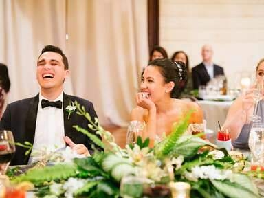 Bride and groom laughing during wedding toast