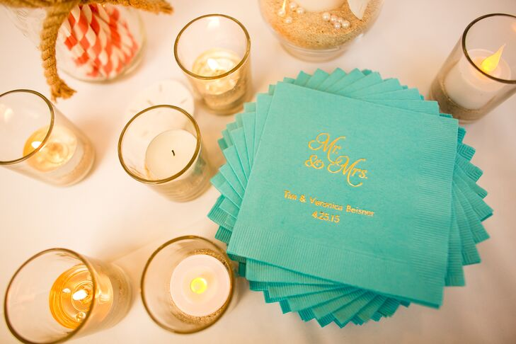 """Teal cocktail napkins accented with gold text read """"Mr. & Mrs. Tim & Veronica Beisner"""" along with their wedding date. Votive candles surrounded the personalized napkins for guests to grab with their drinks."""