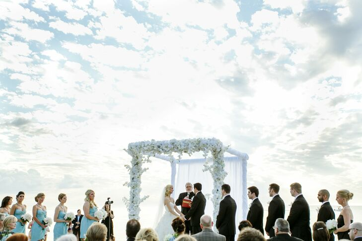 The couple married on the beach, beneath a wedding canopy that was made up of white hydrangeas and phalaenopsis orchids.