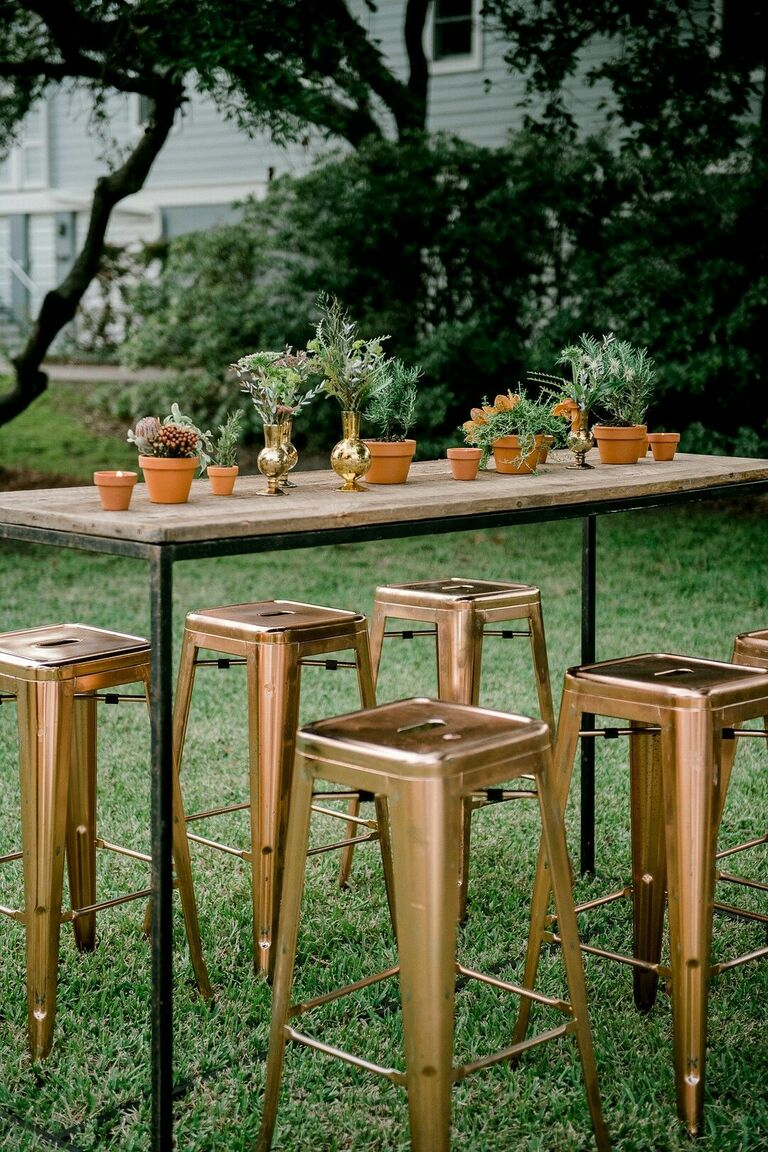 Tall table with potted plant centerpieces and industrial bar stools