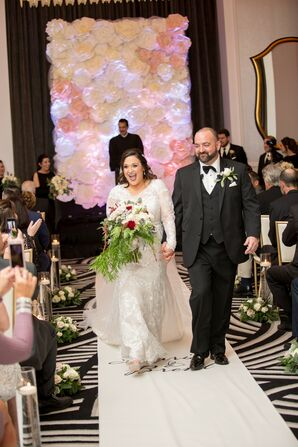 Classic Couple Recessing from Winter Hotel Ceremony with Paper Flower Backdrop
