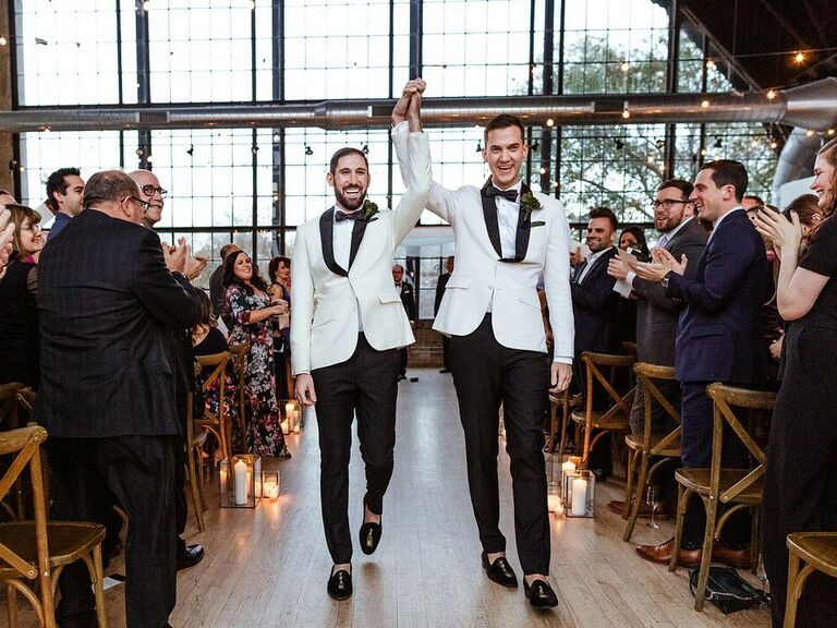 Couple holding hands in air down the aisle