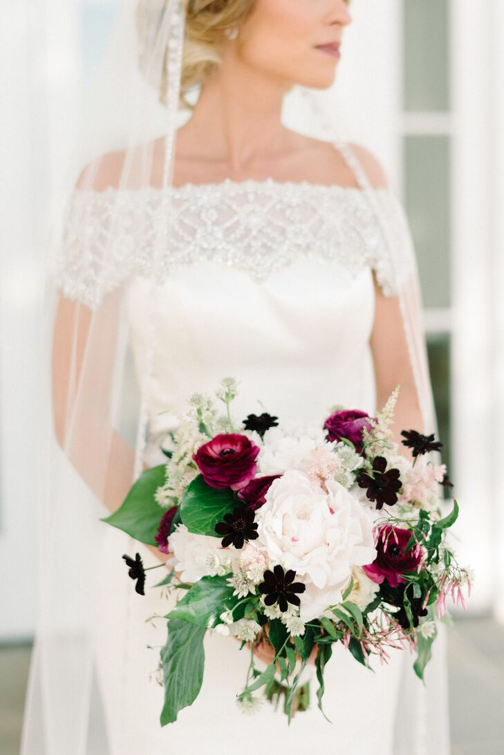 """""""I knew I wanted to incorporate peonies into my bouquet, as well as blush astilbes once I saw them on Pinterest,"""" Sarah says. Keeping this in mind, Anna Rose Floral and Event Design crafted her dramatic arrangement with both flowers and more in their color scheme. A white ribbon wrap gathered organic burgundy ranunculus, black hellebores, white peonies, sprigs of Queen Anne's lace and pink astilbes."""