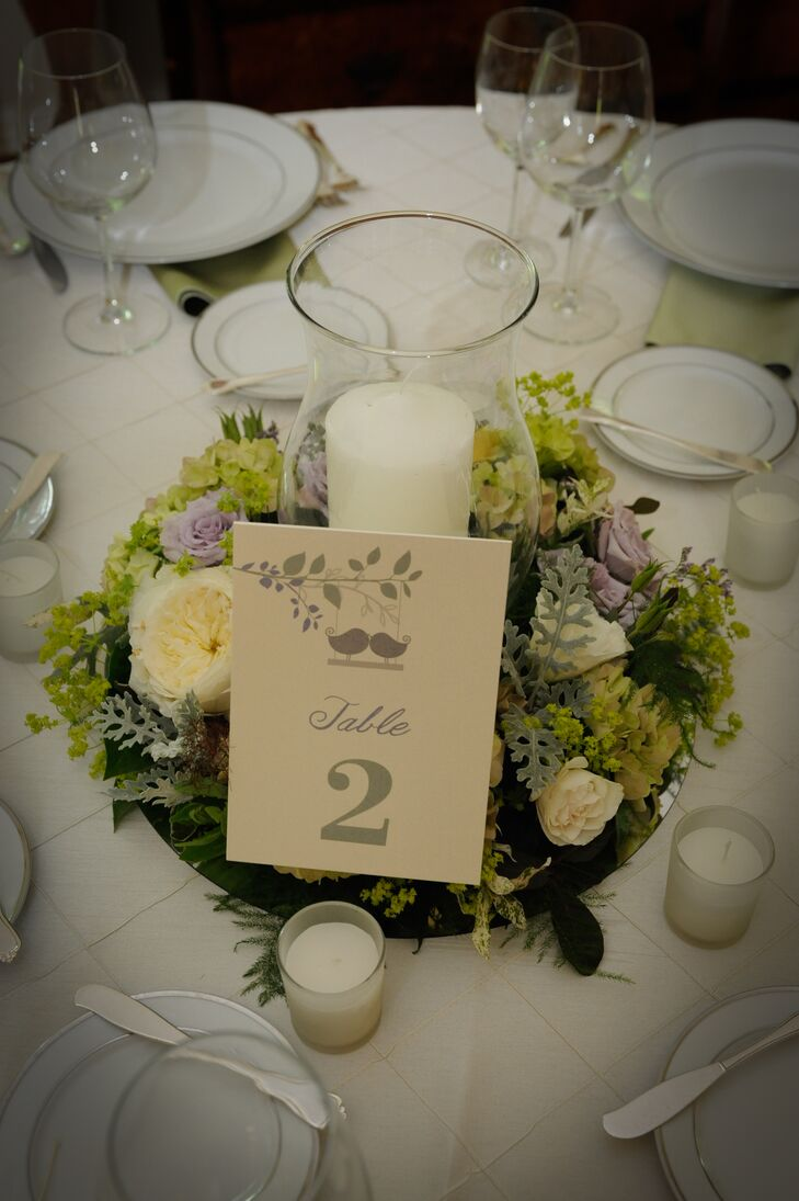 A single ivory candle was surrounded by purple and yellow roses accented with eucalyptus and greens. These pieces that embodied the natural wedding day color palette served as centerpieces for the dining tables. A table number was positioned at the front of the arrangements, which had sage green calligraphy written on ivory stationery. Smaller white candles were scattered around the centerpieces, creating a warm, welcoming glow inside the reception space.