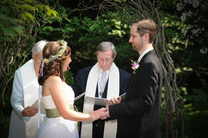 """Christine and Mike stood at the altar shaped by the branch wedding arch and were married outside at The Holden Arboretum in Kirtland, Ohio, by their officiant. Christine wore a sage green sash with her ivory wedding dress, which matched Mike's tie. """"I wanted something simple but elegant, and I wanted to bring in a little thematic color,"""" Christine says. """"I wore a sage green sash that matched my husband's tie and our wedding colors."""""""