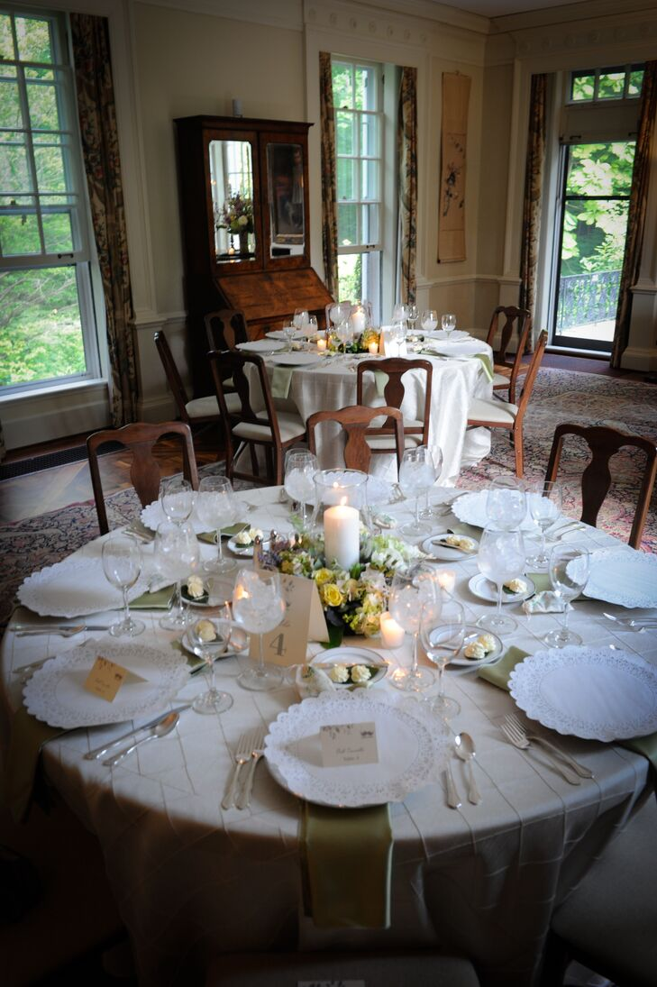 The reception dinner was held inside the Lantern Court Arcade at The Holden Arboretum in Kirtland, Ohio. Round dining tables were dressed in white linens and set with antique dinnerware covered in paper. Yellow and purple flower centerpieces decorated the middle of the tables, which were made up of roses accented with eucalyptus and other greenery.