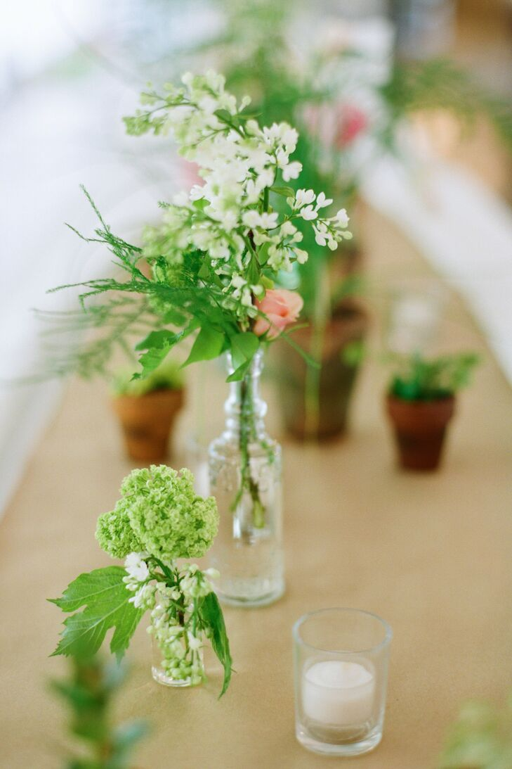 Small, vintage-style bottles filled with an assortment of fresh flowers decorated tables at the reception.