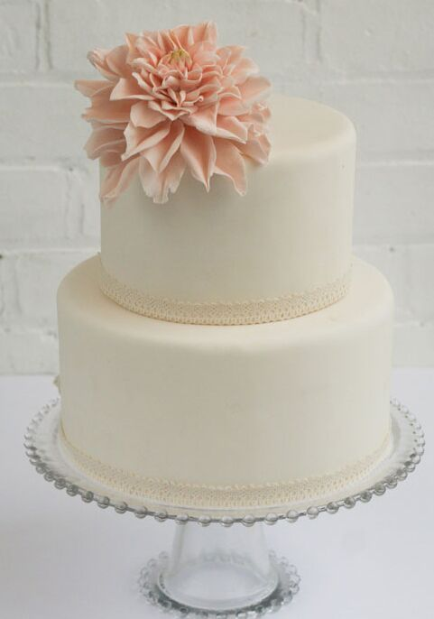 Two-tier white bridal shower cake with small pink dahlia on top