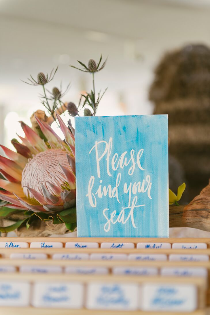 """Calligrapher and illustrator Natalie Soud created Diana and Stephan's tropical-themed invitation suite and inscribed  domino tiles for escort cards. """"I grew up playing dominoes with my mom and my grandfather, so Stephan and I continue that tradition and bring a box of dominoes on every trip we take,"""" Diana says. """"That's why we had everyone's name drawn on the back of a domino with the reverse side's dots indicating their table number."""""""
