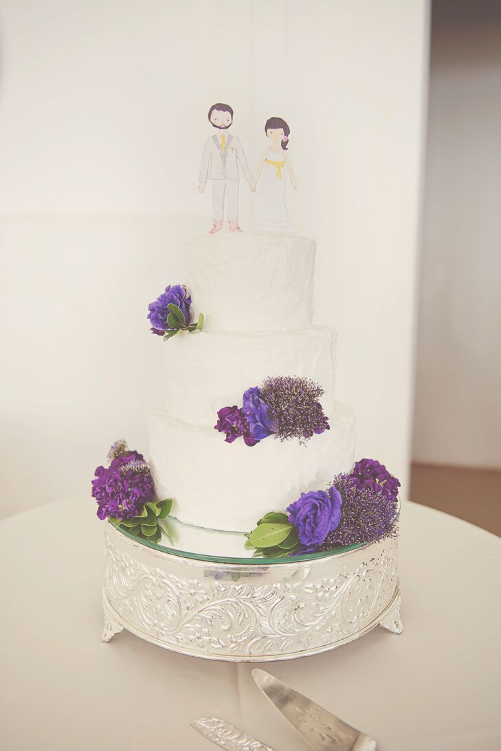 The three-tiered cake, with handmade bride and groom paper dolls as cake toppers, was covered in buttercream and accented with purple flowers.