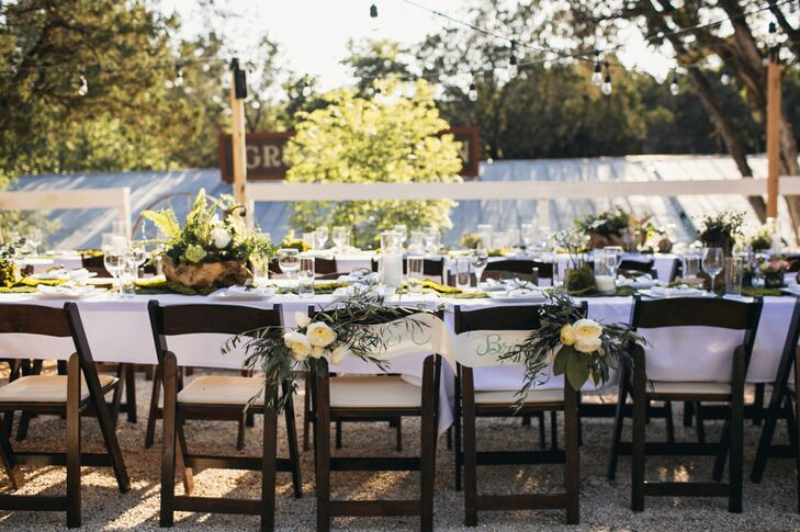 The couple hosted their reception dinner outdoors at dusk under bistro lights. For decor, the couple selected decor and flowers in greens, including moss, ferns and greenery, with pops of blue and hints of bright colors inspired by their road trip.