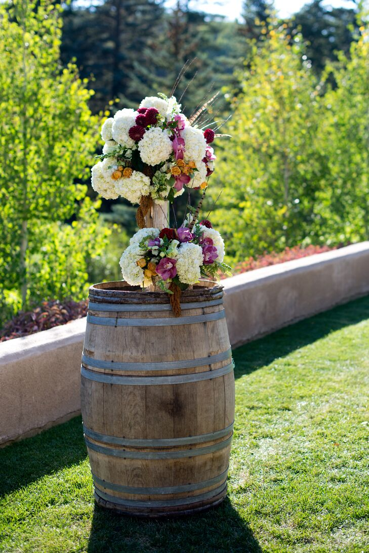 Floral arrangements including hydrangeas, orchids and roses decorated wine barrels at the alter.