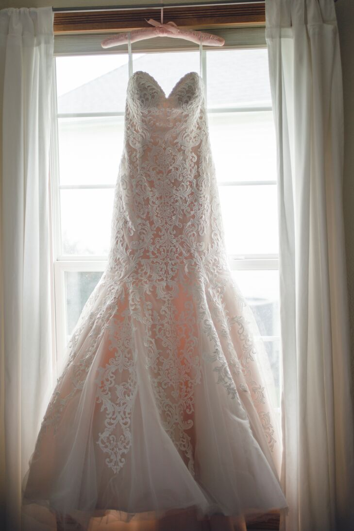 A champagne underlay gave a slight rose hue to the bride's strapless, trumpet-fit lace gown from Allure.