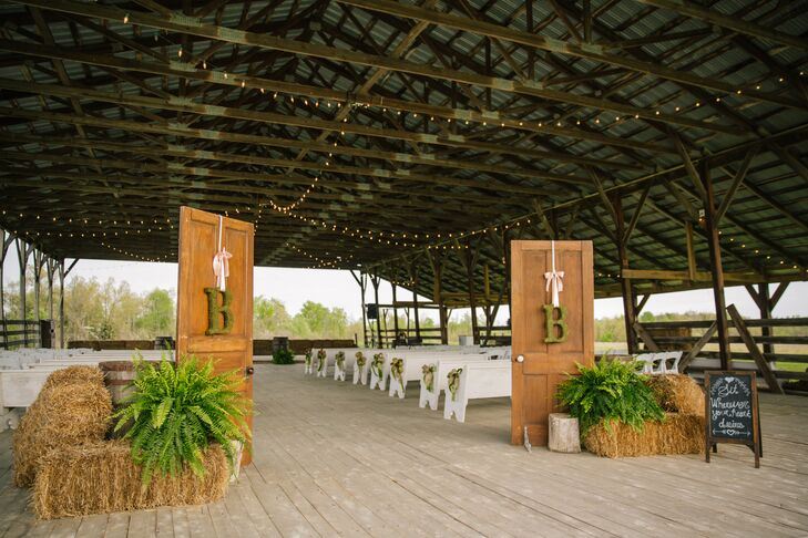 "Nicole and Coleman said ""I do"" in the Ole' Leanin' Barn for its romantic string lighting, old wooden church pews and its protection from the elements. They used old whiskey barrels and church doors at the aisle entrance, and strung moss-covered ""Bs"" at the entrance for a personal touch."