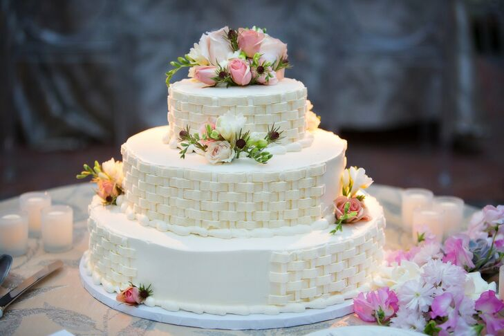 The three-tier cake had a basket-weave design and was decorated with fresh roses.