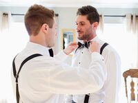 Best man helping groom with bow tie before wedding