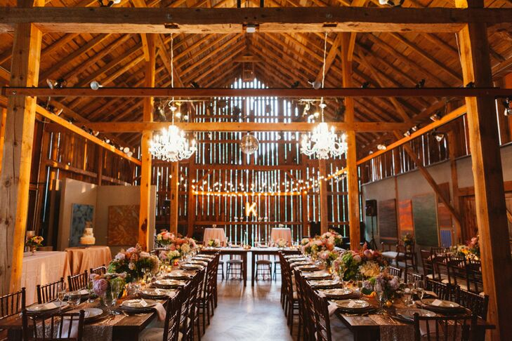 The reception took place in the Woodwalk Gallery's spacious, historic barn, a rustic space that provided the couple with a blank canvas to make their own. Using a color palette of petal pink, mint and gold, the pair transformed the venue into the picture of glamour and elegance. Sequin-studded table runners, mercury glass accents, gilded cutlery and glitter-flecked chargers added a refined edge to the room, while fluffy arrangements of peonies, flickering candlelight and whimsical script table numbers filled the room with romance and life.rn