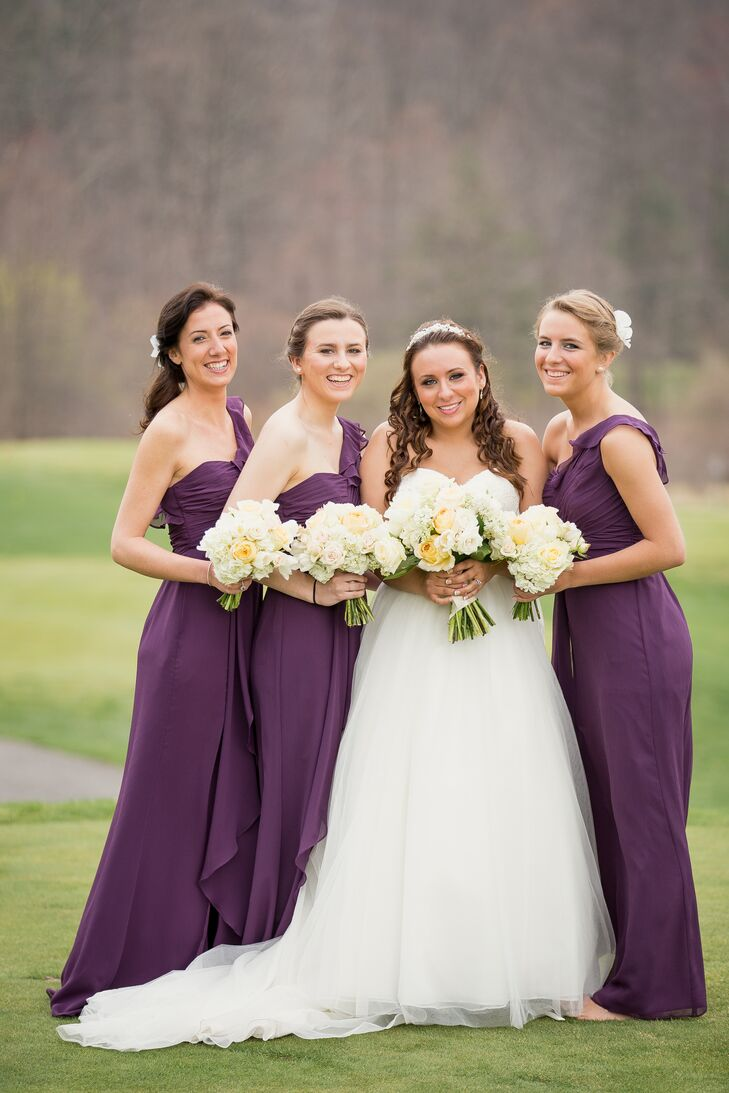 With Sarah's favorite color in mind, each bridesmaid wore a floor-length eggplant dress from David's Bridal for the wedding. A ruffle detail on the skirt and one-shoulder strap added a fun accent to the gown as each woman wore her hair in either an updo or side-swept hairstyle with a white accent.