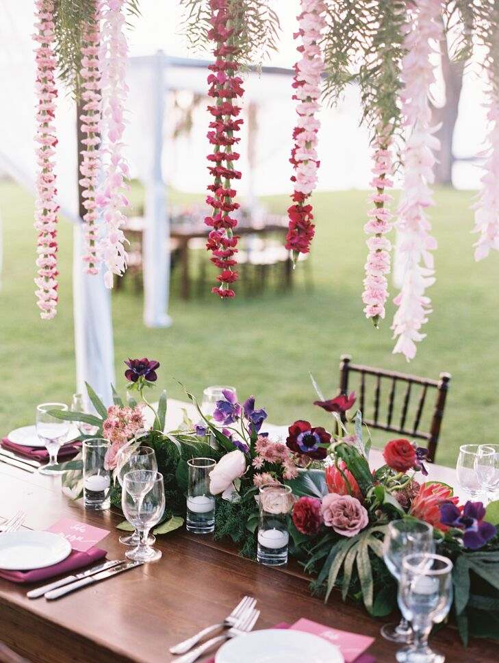 Pink and burgundy flower lei hung from canopies above the large farmhouse tables. Centerpieces were a mix of candles, tropical blossoms and green ferns.