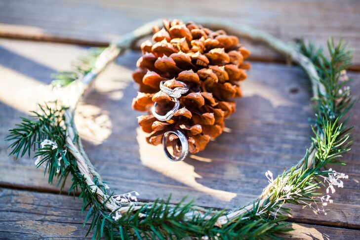 The silver engagement ring and wedding rings exchanged at the ceremony rested on top of a brown pinecone; many pinecones were used for the bouquets and boutonnieres.
