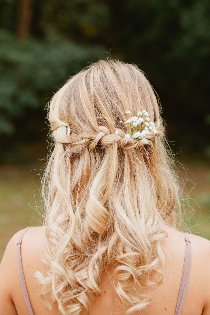 In keeping with a rustic country theme, the bride and groom wove cotton and baby's-breath throughout their wedding ceremony and reception. Here, the bride wears baby's-breath in an undone braid.