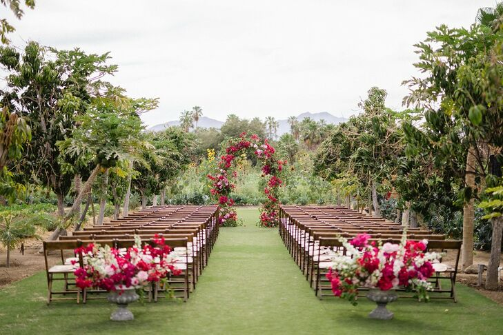 Romantic Outdoor Ceremony with Pink Flowers and Wedding Arch at Flora Farms in San José del Cabo, Mexico