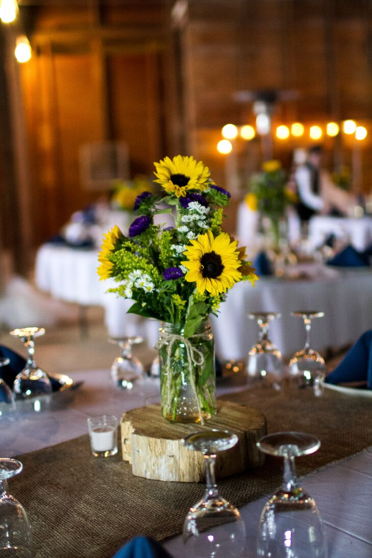 Centerpieces were made up of sunflowers, daisies and purple zinnias in mason jars. The flower arrangements were displayed on tree rings that sat at the center of the burlap table runners.