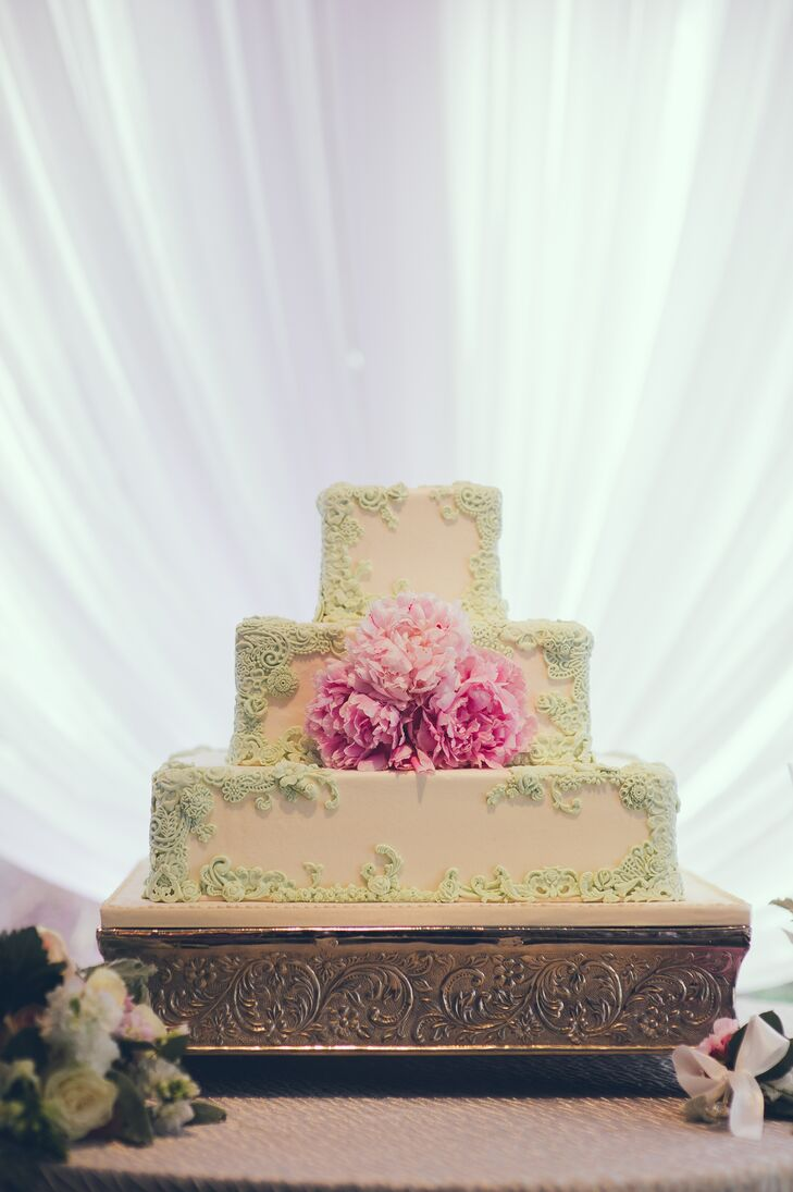 The couple's wedding cake featured three square ivory tiers framed in light sage green lace with a trio of bright pink peonies in the center.