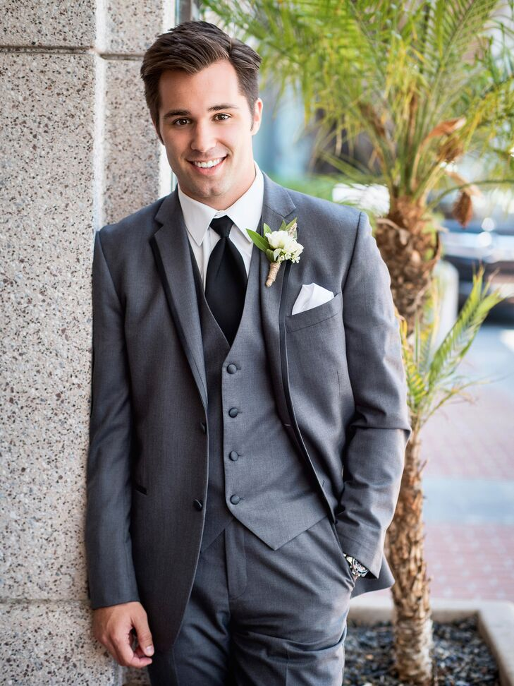 Kyle sported a three-piece suit in a charcoal gray color for the wedding day, worn with a black tie and a white collared shirt that was complemented by a matching pocket square. There was an ivory rose boutonniere accented with leaves pinned to the lapel of his jacket.