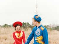 Couple walking in field wearing traditional Vietnamese ao dai