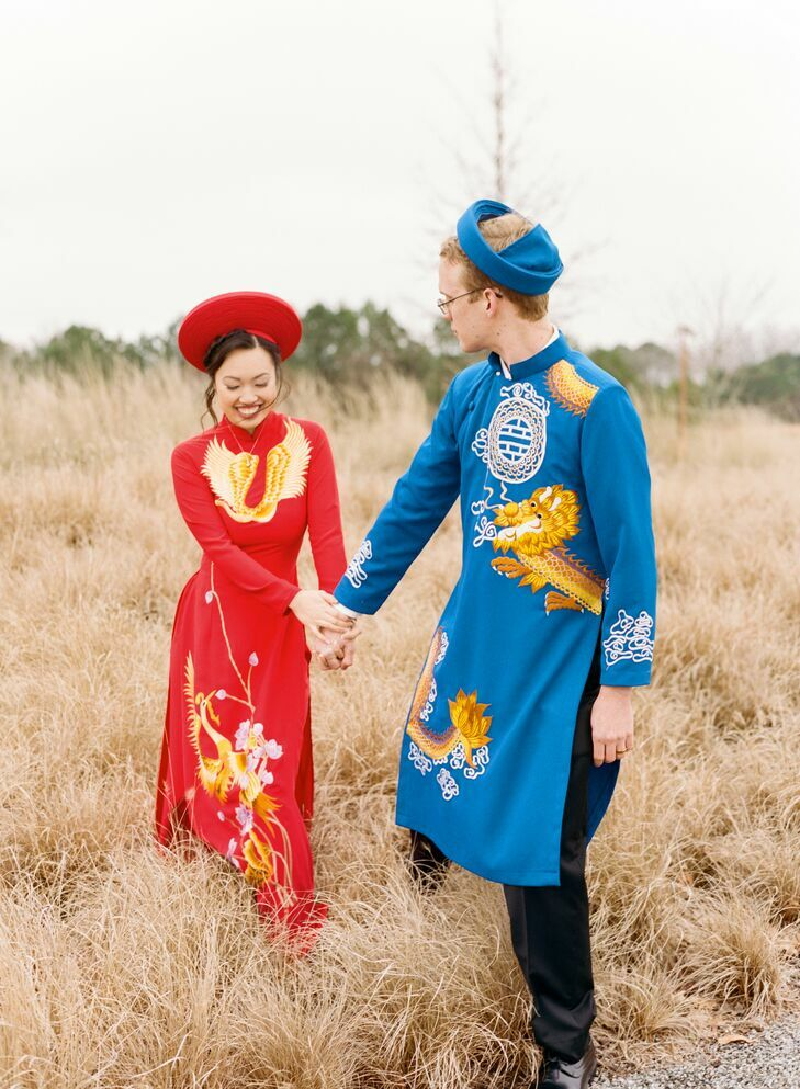 Couple walking in field wearing traditional Vietnamese ao dai