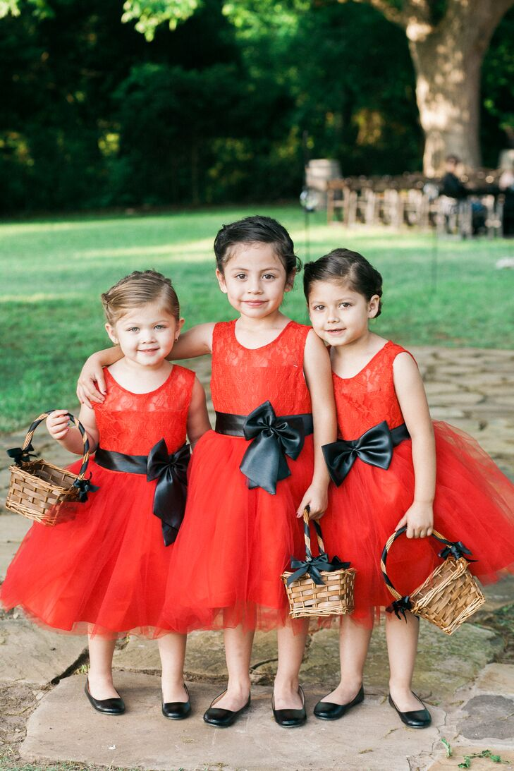 These flower girls looked absolutely adorable. Each wore a red dress with a lace illusion neckline, a full tulle skirt and a black sash to accent.