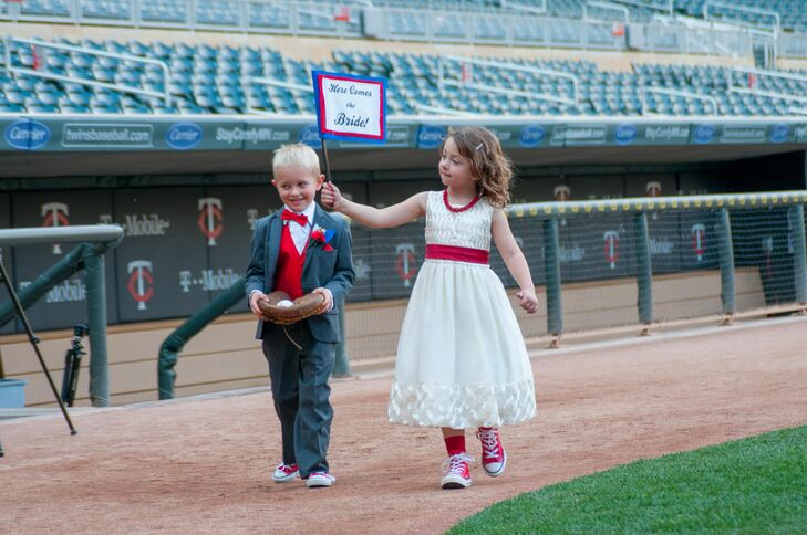 "The girl attendant carried a small sign that said ""Here Comes the Bride,"" while the ring bearer carried the rings in a baseball glove."