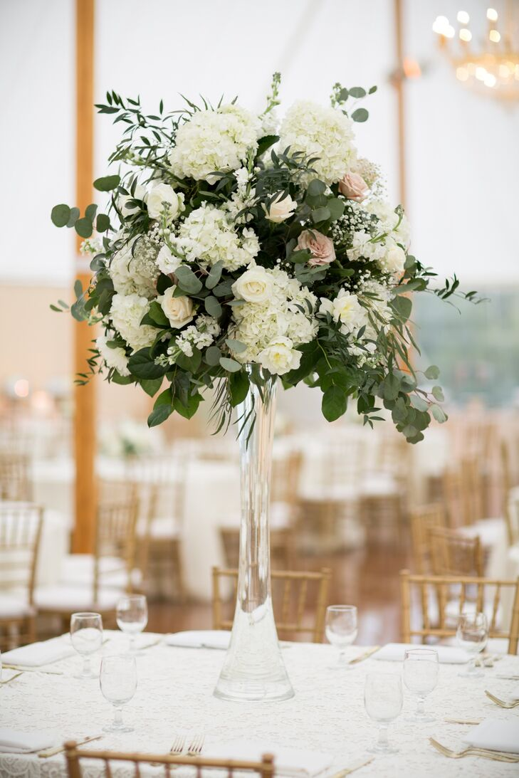 To add texture and drama to the reception decor, Fiore Fine Flowers created tall and low centerpieces for the tables. The tall arrangements were displayed atop sleek glass pedestals and featured roses, peonies, hydrangeas and eucalyptus, while the low centerpieces had a comparable flower-to-greenery ratio, containing both eucalyptus and wispy greenery.