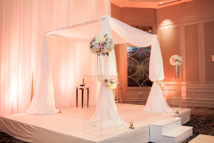 Leah and Grant's romantic chuppah was decorated with flowing sheer white drapery with blush blooms adorning the front poles of the chuppah.