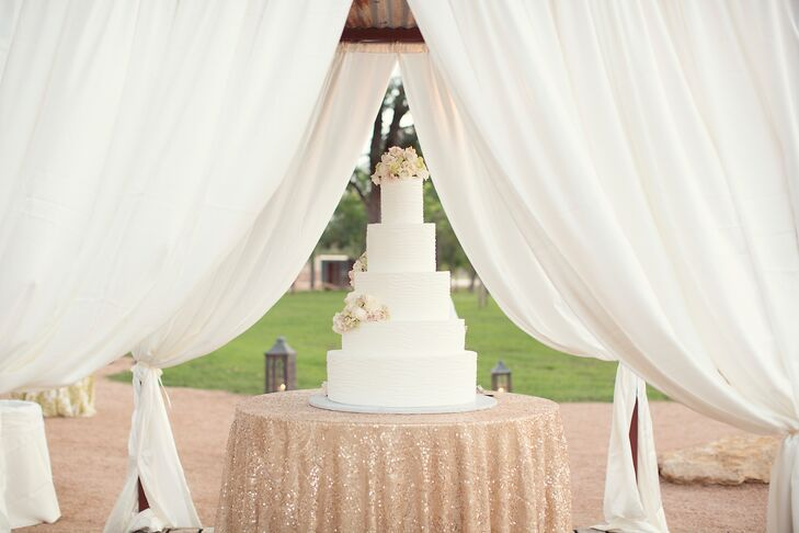 Lucy and Will wanted to go classic for her wedding cake, so they went for a five-tier textured white buttercream white cake. It had her new monogram and scattered white and green flowers. The sparkly gold cake table surrounded by white drapery created a dramatic display.