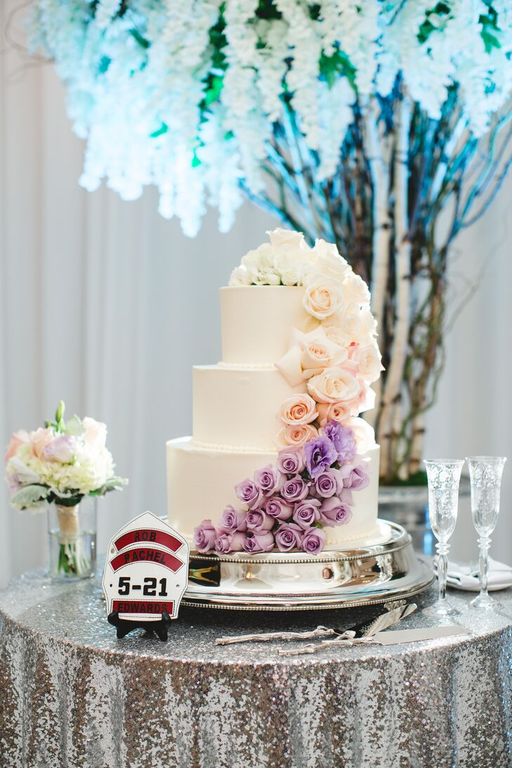 """The couple's three-tier cake was frosted in Swiss buttercream and incorporated two kinds of cake flavors: vanilla genoese with lemon and raspberry mousse for Rachel and red velvet for Rob. The cake was topped with cascading blooms in white, pink and purple. """"Instead of a cake topper, we opted for a custom firefighter helmet shield with our names and wedding date in homage to Rob's job,"""" Rachel says."""