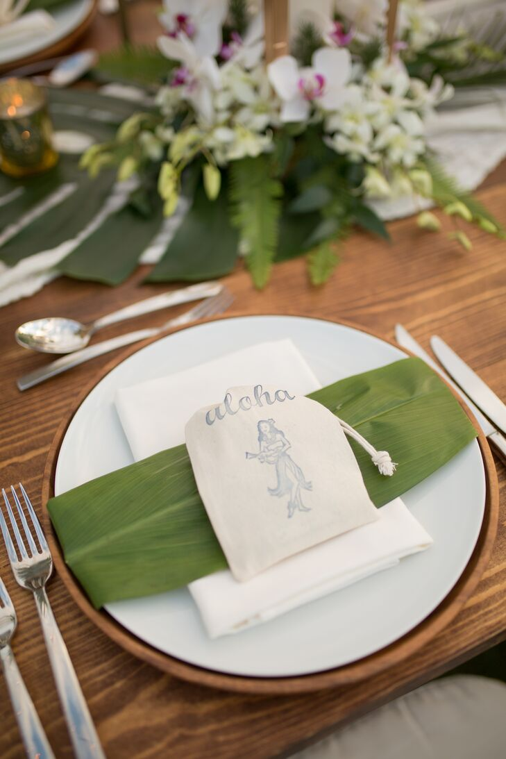 The banquet table was topped with fern fronds and pineapples. Each table setting included a menu handwritten in gold calligraphy on large leafs as well as a small Hawaiian-themed favor.