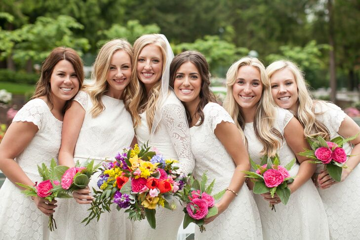 Each bridesmaid held large pink garden roses arranged into bouquets, complementing Emily's larger bouquet filled with an assortment of colorful blooms.
