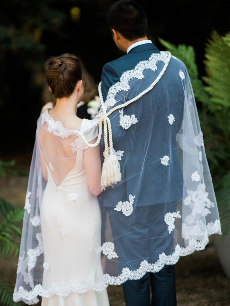 Bride and groom wearing veil and rope during traditional Lasso ceremony