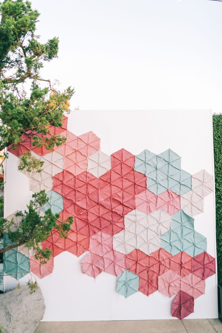 A stitched fabric installation resembling a quilt served as a photo booth backdrop at the reception at L'Auberge Del Mar in Del Mar, California.