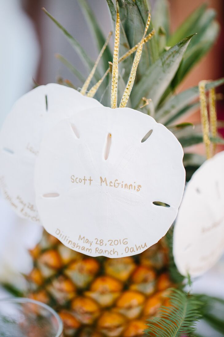 Sand dollars inscribed with gold writing and strung on gold ribbon were used as place cards for the reception at Dillingham Ranch in Waialua, Hawaii. They doubled as personalized wedding favors.