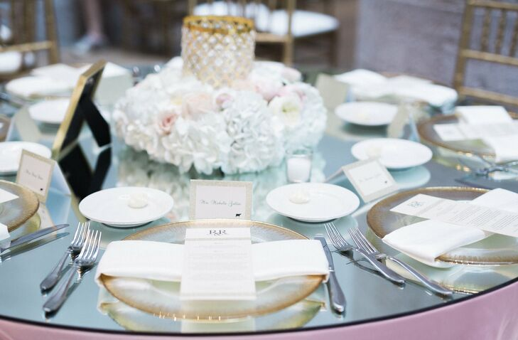 Tables featured varying styles of modern floral arrangements with gold and crystal hurricane candleholders surrounded by a square floral wreath.