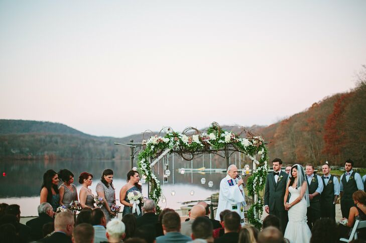 """The lakeside ceremony took place just before sunset under a branch archway decorated with flowers and hanging votive candles. """"I wanted to remember those who had passed. I collected pictures of those family members, put each one in a mason jar with LED candles and hung the jars from the arch,"""" Elaine says."""