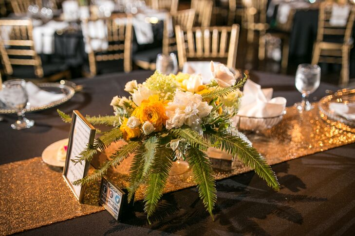 This dining table had a low white and yellow centerpiece filled with roses, chrysanthemums and ranunculus, positioned on top of a bed of fern leaves. Tall centerpieces with similar flower combinations decorated dining tables at the reception as well.